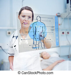 Nurse touching screen displaying blue human form in hospital...