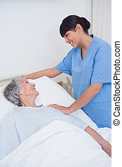 Nurse touching the shoulder of a patient in hospital ward