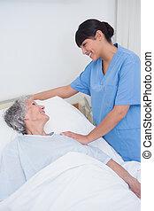 Nurse touching the shoulder of a patient