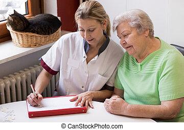 blond nurse visiting a senior patient at home