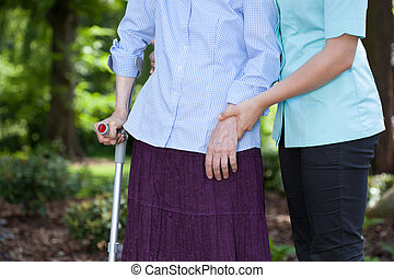 Nurse walking with a female patient with a crutch - Close-up...