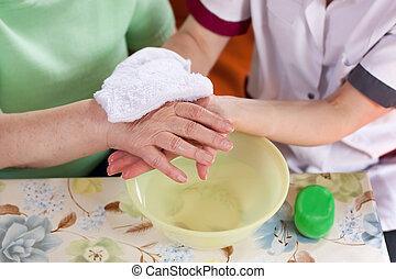 young nurse washes hands of an elderly woman