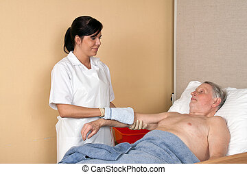 nurse washing a patient - a nurse washes a patient in a...