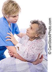 nurse with a senior woman - nurse helps the senior woman get...