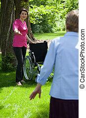 Nurse with elderly woman in garden of retirement home
