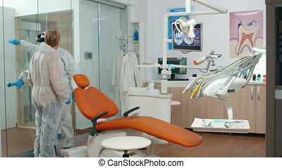 Nurse with protection suit inviting senior woman in consultation dental room for teeth examination during coronavirus. Orthodontic stomatology checkup in new normal reality covid pandemic outbreak