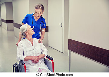 nurse with senior woman in wheelchair at hospital -...