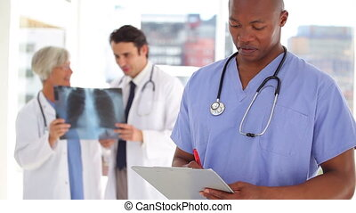 Nurse writing on a clipboard in front of doctors in a...