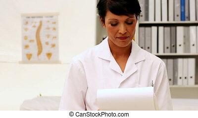 Nurse writing on clipboard