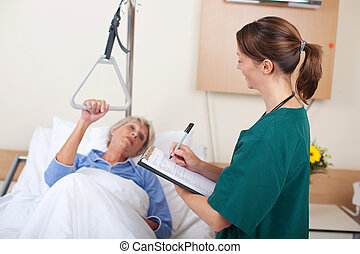 Nurse Writing On Clipboard While Looking At Patient