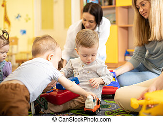 Nursery babies playing together with moms in a play room