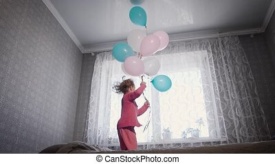 Nursery in the afternoon. The child prepares for a day dream. The baby in a pink pajamas jumps on a bed in excellent mood.