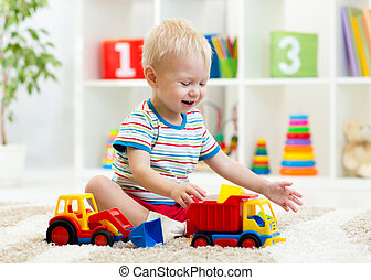 nursery kid boy toddler playing with toys in kindergarten