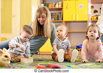 Nursery teacher looking after children in daycare. Little kids toddlers play together with developmental toys.
