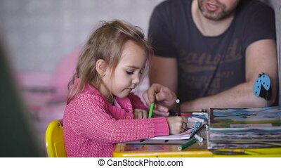 Nursery. The baby with the father at a drawing table. The girl with the man paint a drawing album. In an album the drawing of a lodge. On a table children's books