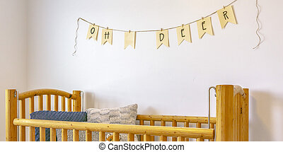 Nursery with wooden crib and bunting on the wall