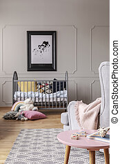 Nursery with wooden crib with cushions and small pink table with toys, real photo with mockup on the grey wall