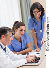 Nurses and doctor looking at laptop