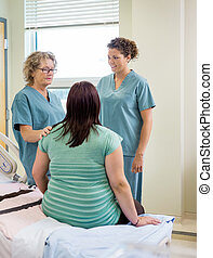 Nurses And Pregnant Woman Communicating In Hospital