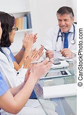 Nurses applauding a doctor