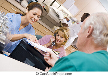 Nurses Discussing A Clipboard At The Reception Area In A Hospital
