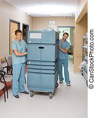 Nurses Pushing Trolley In Hospital Hallway