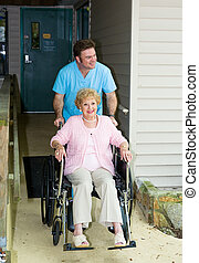 Nursing Home - Accessible - Orderly takes a disabled senior...