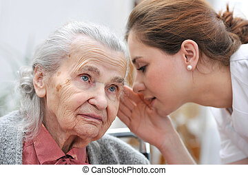 Nursing home - Female nurse is speaking in senior woman ear