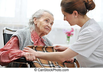 Nursing home - Female nurse is taking care of the senior...