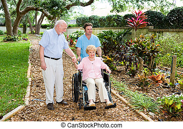 Nursing Home Gardens - Senior woman in a wheelchair being...
