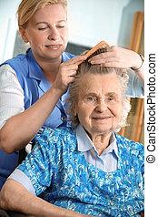 nursing home - Nurse dressing the hair of a senior woman