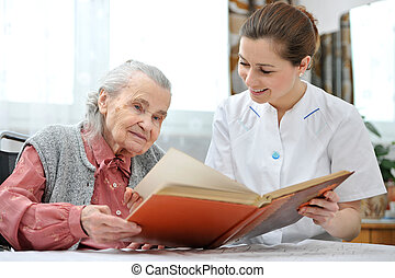 Nursing home - Senior woman and nurse looking together at...