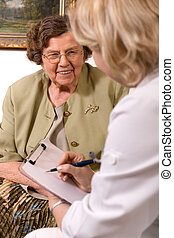 Senior woman is visited by her doctor or caregiver at home. In the background is a picture from my portfolio
