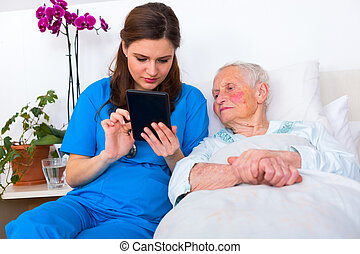 Caring nurse showing a digital tablet to an elderly woman in a nursing home.