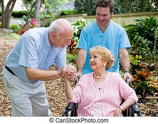 Nursing Home Visit - Senior husband visiting his disabled...