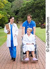 nursing staff pushing patient