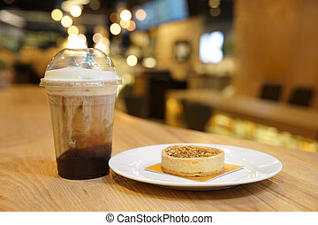 nut caramel moon cake with ice latte coffee beside, on the wood table.