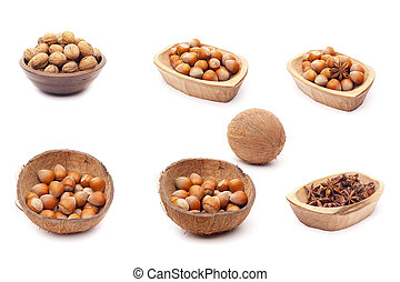 Nut collection of walnut, hazelnut, mag nut in rustic wooden bowls coco bowls, isolated over white background.