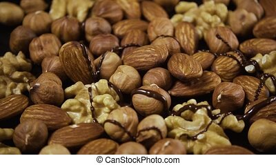 Nut mixture is poured with chocolate. High speed - Nut...