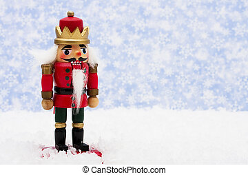 Nutcracker sitting on snow with snowflake background,...