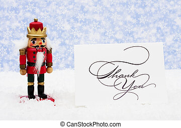 Nutcracker sitting on snow with thank you card on a...