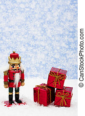 Nutcracker sitting on snow with three red presents on a...