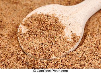 Nutmeg ground (Myristica fragrans) texture and wooden spoon...