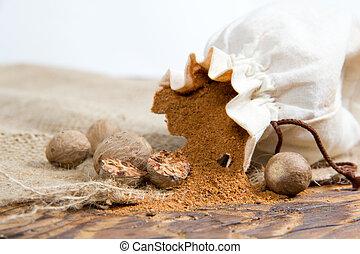 Nutmeg - Photo of bag full of nutmeg powder on burlap with...