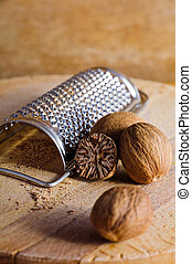 Nutmeg and grater on a wooden background