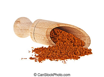 Nutmeg powder in wooden shovel on a white background