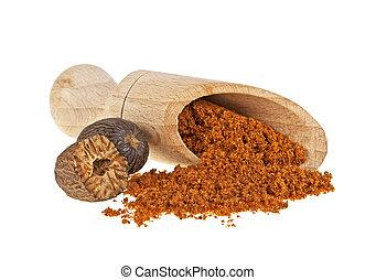 Nutmeg powder in wooden shovel on a white backgroun