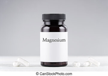 nutritional supplement magnesium bottle and capsules on gray background