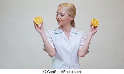 nutritionist doctor healthy lifestyle concept - holding orange fruit.