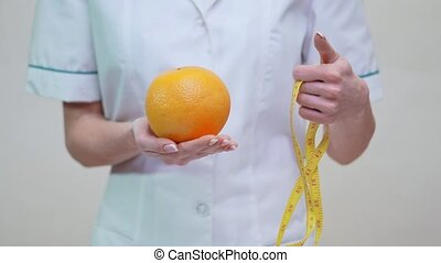 nutritionist doctor healthy lifestyle concept - holding orange fruit